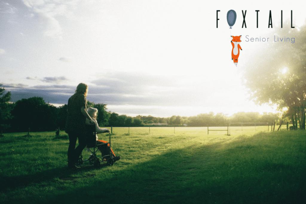 Woman pushes man in a walker through a field