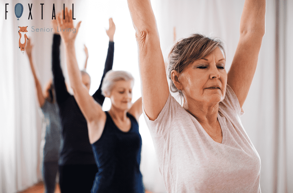Senior women and man performing yoga exercises as a group in a bright room in an assisted living facility.