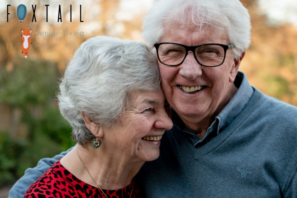 A happy senior couple hugging each other in a park