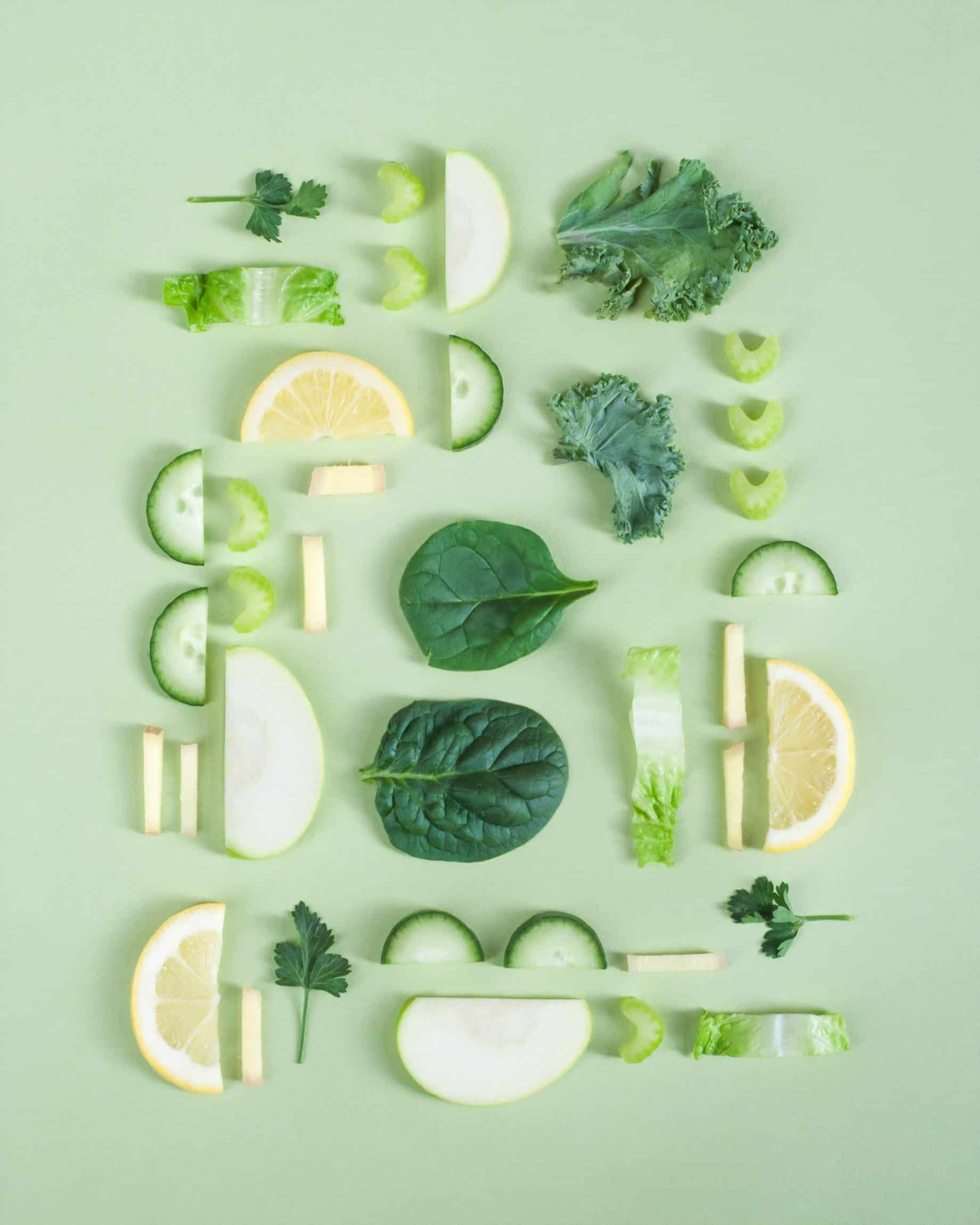 different green fruits and vegetables that are cut up and layed out in an aesthetically appealing way.