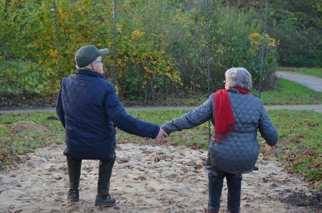 An elderly couple that is holding hands and swinging at a park.
