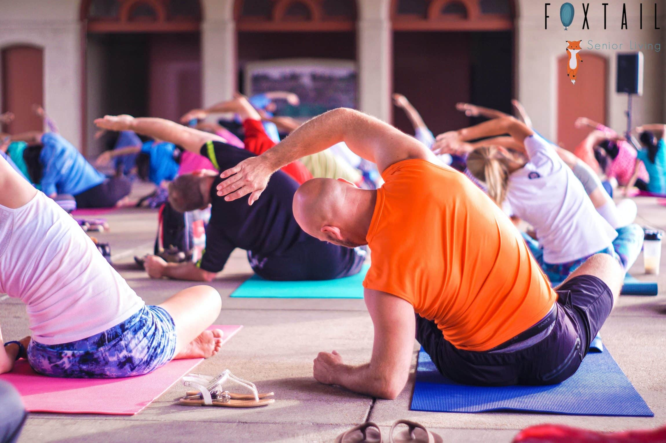Man in an orange shirt doing a yoga pose in a yoga class.