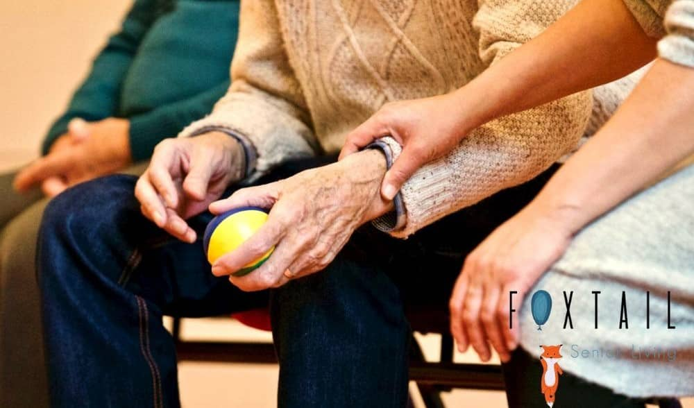Elderly man squeezing a therapy ball