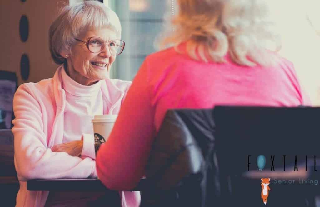 Senior woman talking to a friend with coffee