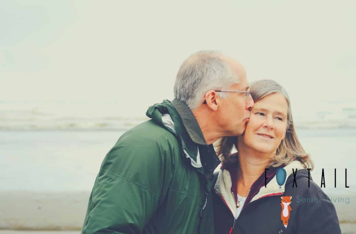 Senior man kissing his wife on the beach