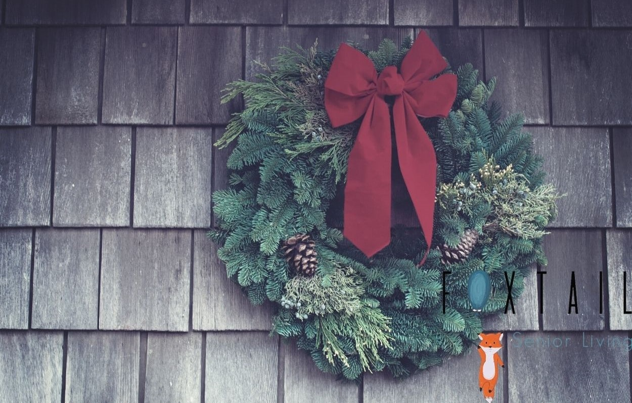 Christmas wreath with a red bow hanging on a shingle wall