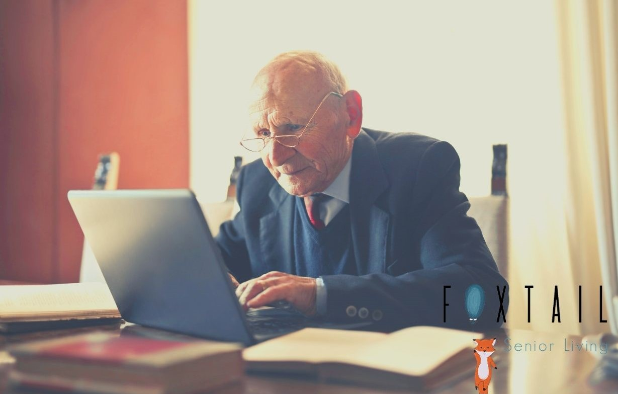 Senior man with glasses and a suit working on his computer