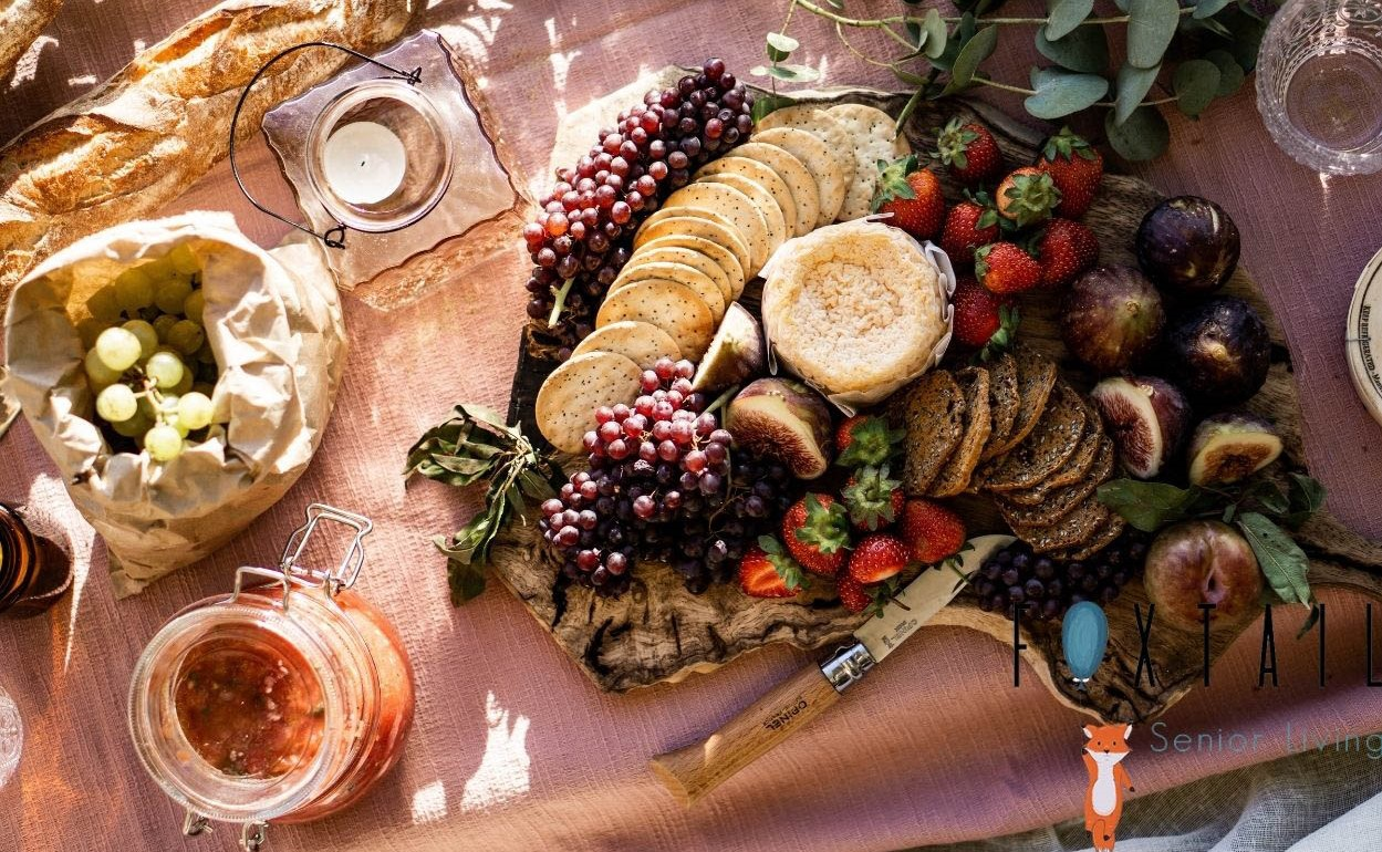 Picnic spread with fruit, cheese, bread, crackers, and a blanket and knife