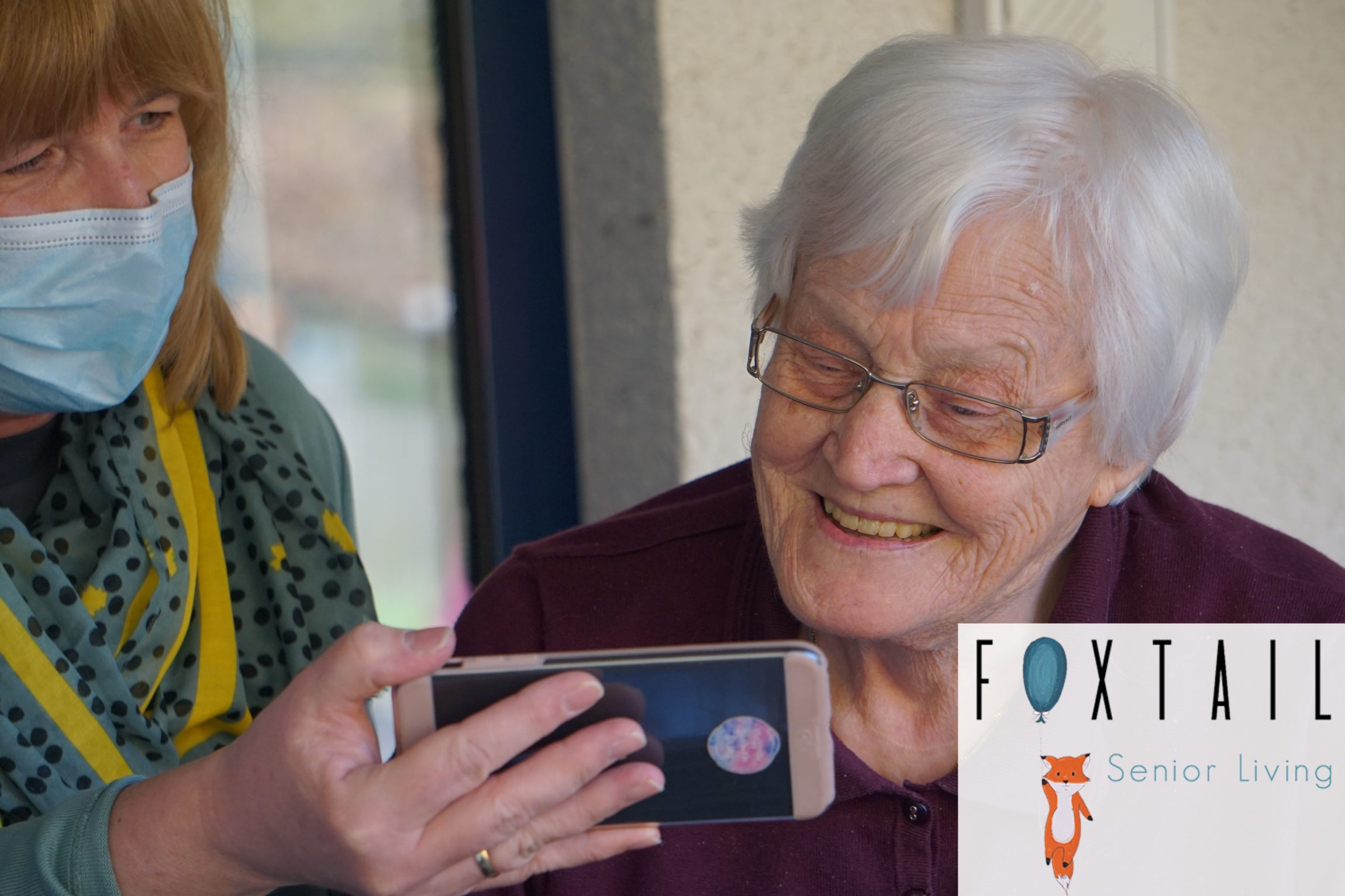 A masked assisted living facility staff member showing a resident something on a phone