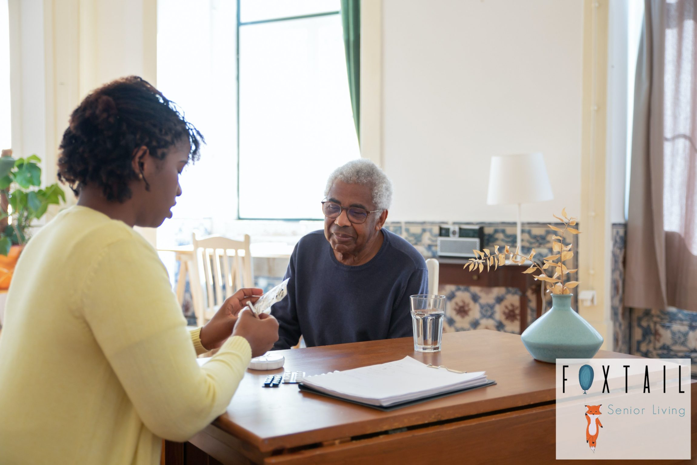 A lady in a yellow sweater giving a man in a black sweater his daily pills at a table.